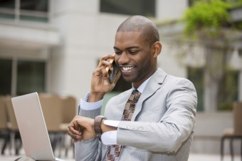 Closeup handsome young businessman working with laptop outdoors talking on mobile phone looking at his wristwatch. Time is money